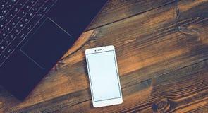 Espace de travail avec l'ordinateur portable et le smartphone sur le bureau en bois dur Photo stock