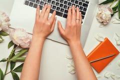 Espace de travail avec l'ordinateur portable et les mains femelles Photographie stock