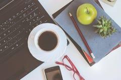 Espace de travail avec l'ordinateur portable, la tasse de café et les livres, sur la table blanche Photo libre de droits
