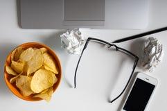 Espace de travail avec l'ordinateur portable, le papier chiffonné et la cuvette de puces sur la table en bois Concept de mauvaise Photo stock