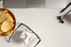 Espace de travail avec l'ordinateur portable, le papier chiffonné et la cuvette de puces sur la table en bois Concept de mauvaise Images libres de droits