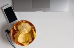 Espace de travail avec l'ordinateur portable, le papier chiffonné et la cuvette de puces sur la table en bois Concept de mauvaise Image stock