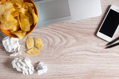 Espace de travail avec l'ordinateur portable, le papier chiffonné et la cuvette de puces sur la table en bois Concept de mauvaise Photographie stock libre de droits