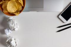 Espace de travail avec l'ordinateur portable, le papier chiffonné et la cuvette de puces sur la table en bois Concept de mauvaise Photo libre de droits