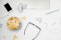 Espace de travail avec l'ordinateur portable, le papier chiffonné, la papeterie et les puces Photo stock