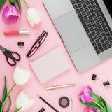 Espace de travail avec l'ordinateur portable, les fleurs de tulipes, les accessoires et le journal intime sur le fond rose Vue su Image libre de droits