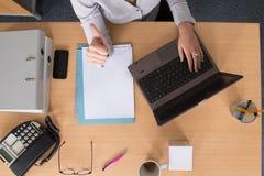 Espace de travail avec l'ordinateur portable, les mains de la fille, carnet, configuration plate Photos libres de droits