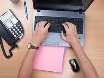 Espace de travail avec l'ordinateur portable, les mains de la fille, carnet, dossier Image libre de droits