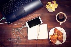 Espace de travail avec l'ordinateur portable, smartphone, croissant, cofee sur un en bois Image libre de droits