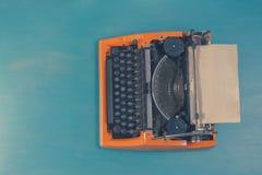 Espace de travail avec la machine à écrire d'orange de vintage Photo libre de droits