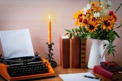 Espace de travail avec la machine à écrire d'orange de vintage Bouquet des fleurs d'été, des bougies et de vieux livres Photographie stock