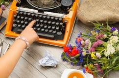 Espace de travail avec la machine à écrire orange de vintage avec la main de l'auteur Bouquet des fleurs de champ et de la tasse  Photographie stock