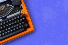 Espace de travail avec la machine à écrire orange de vintage sur un fond bleu Photos stock