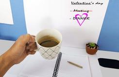 Espace de travail avec la main d'un homme d'affaires tenant une tasse de café dessus Photographie stock libre de droits