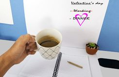 Espace de travail avec la main d'un homme d'affaires tenant une tasse de café dessus Photographie stock
