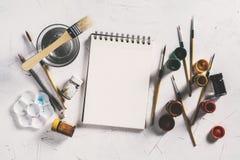 Espace de travail avec la peinture de couleur de carnet et d'affiche, brosses, vieilles Photo stock