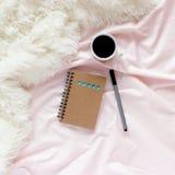 Espace de travail avec le bloc-notes, stylo, tasse de café dans le lit Concept de mode de vie Photos libres de droits