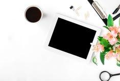 Espace de travail avec le comprimé, les accessoires de bureau, le café et le bouquet de Image stock