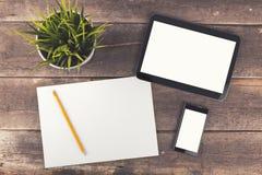 Espace de travail avec le comprimé numérique, le téléphone et le papier blanc sur t en bois Photo libre de droits