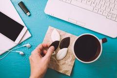 Espace de travail avec le journal intime, usine, écouteurs, café, crayons sur la table bleue la main du ` s de fille prend des bo photo stock