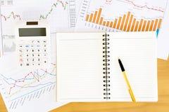 Espace de travail avec le livret, le stylo et les graphiques Ba en bois de table Photographie stock