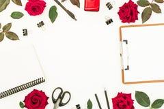 Espace de travail avec le presse-papiers, le carnet, les accessoires et les fleurs rouges sur le fond blanc Concept de Blogger Co Image stock
