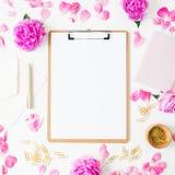Espace de travail avec le presse-papiers, le carnet, le stylo, l'enveloppe et les roses roses sur le fond blanc Configuration pla Photographie stock libre de droits