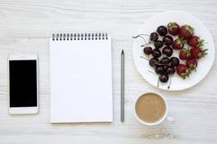 Espace de travail avec le smartphone, les fraises, les cerises, le bloc-notes et le l Image stock