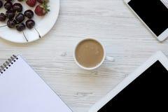 Espace de travail avec le smartphone, les fraises, les cerises, le bloc-notes et le latte au centre sur le fond en bois blanc Photo libre de droits