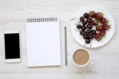 Espace de travail avec le smartphone, les fraises, les cerises, le bloc-notes et le latte sur le fond en bois blanc Photos stock