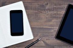 Espace de travail avec le téléphone, le comprimé numérique, le bloc-notes et le stylo Photos stock