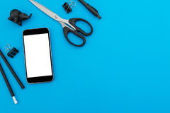Espace de travail avec les accessoires noirs : téléphone portable, crayon, stylo, ciseaux sur le fond bleu Bureau plat de configu Photos libres de droits