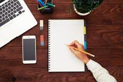 Espace de travail avec les mains de la femme tenant le crayon Photographie stock libre de droits