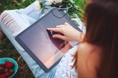 Espace de travail avec les mains de la fille, ordinateur portable, bouquet des fleurs de pivoines, café, fraises photographie stock libre de droits