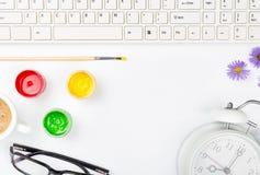 Espace de travail blanc avec le clavier, peinture avec la brosse, verres, café Images stock