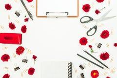 Espace de travail de bureau d'indépendant avec le presse-papiers, le carnet, les fleurs rouges et les accessoires sur le fond bla Photographie stock