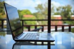 Espace de travail conceptuel, ordinateur portable sur la table et fond vert de jardin Photo stock