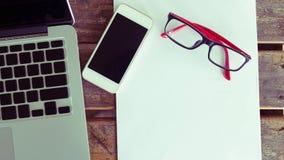 Espace de travail créatif avec le blanc et le téléphone portable de livre blanc Image libre de droits