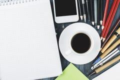 Espace de travail créatif avec le smartphone et les approvisionnements Images stock