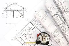 Espace de travail d'architectes avec des rouleaux de plans et de ruban métrique Image libre de droits