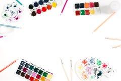 Espace de travail d'artiste avec l'aquarelle, les crayons de couleur et les brosses d'isolement au fond blanc Configuration plate Photographie stock libre de droits