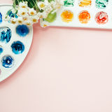Espace de travail d'artiste avec la camomille blanche de bouquet, palettes d'aquarelle Photos libres de droits