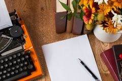 Espace de travail d'auteur avec la machine à écrire orange de vintage sur le fond brun Image stock