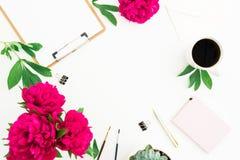 Espace de travail de Blogger ou d'indépendant avec le presse-papiers, le carnet, les fleurs de pivoine et la tasse de café sur le Photo stock