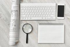 Espace de travail de bureau avec le dessin architectural, le clavier, le smarthphone, le livre propre et la loupe sur la surface  Image libre de droits