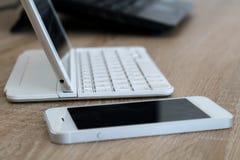Espace de travail de bureau avec le téléphone portable et le comprimé Photographie stock libre de droits