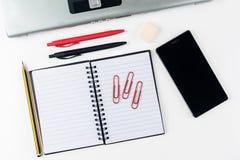 Espace de travail de bureau sur le fond blanc avec le smartphone et l'ordinateur portable Photographie stock libre de droits