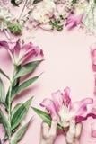 Espace de travail de fleuriste Les mains femelles tenant le beau lis rose fleurit sur la table en pastel avec l'équipement de déc Image libre de droits