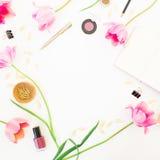 Espace de travail de siège social avec le carnet, les cosmétiques, les tulipes roses et les accessoires sur le fond blanc Trame r Photos stock