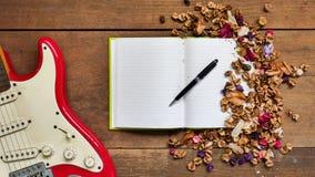 Espace de travail de vue supérieure avec le carnet, stylo, guitare électrique et sec Photo libre de droits